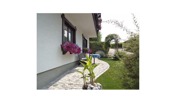 Blick auf das Haus von der Seite, vor dem Haus Gartenbank, Tisch, Blumen, Wiese