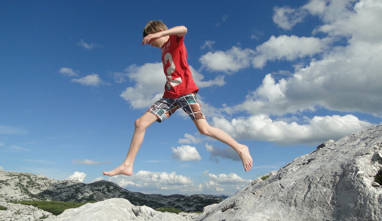 Boy jumps over the rocks