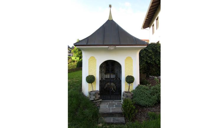 Blick auf die Kapelle, seitlich Sträucher