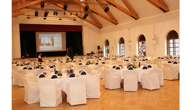 Festaal - festively set tables, chairs with nice cover, in the front the stage with a screen