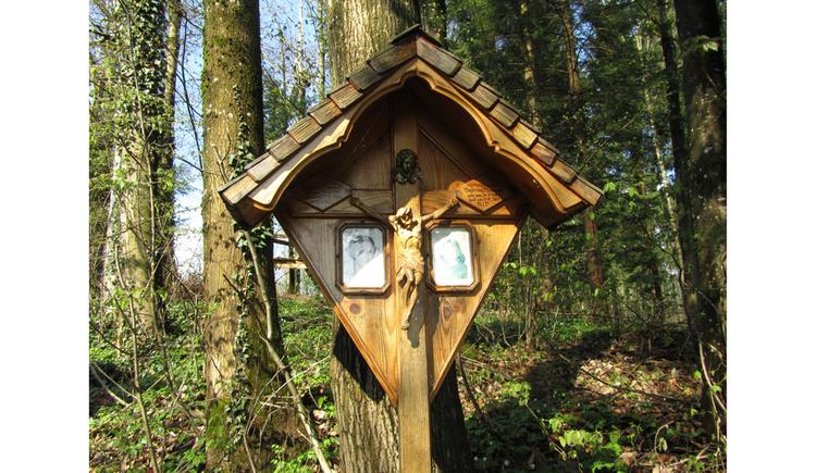 Blick auf ein Holzkreuz, im Hintergrund Wald
