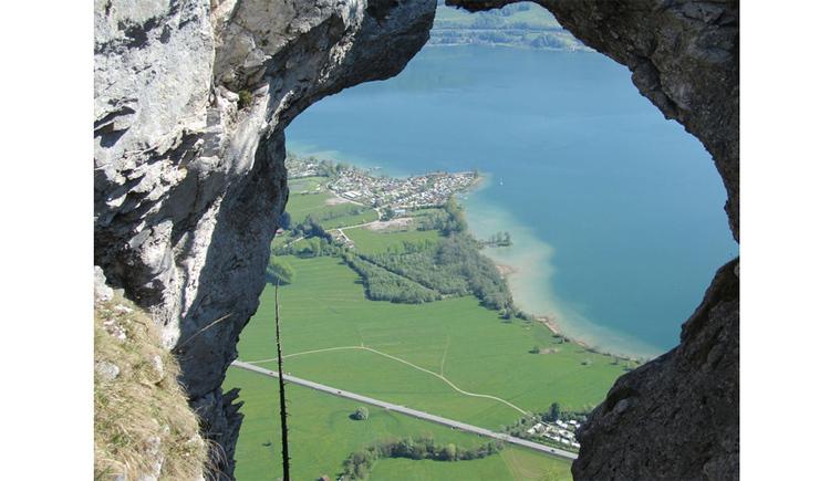 Blick auf die Landschaft und den See durch ein Loch im Berg