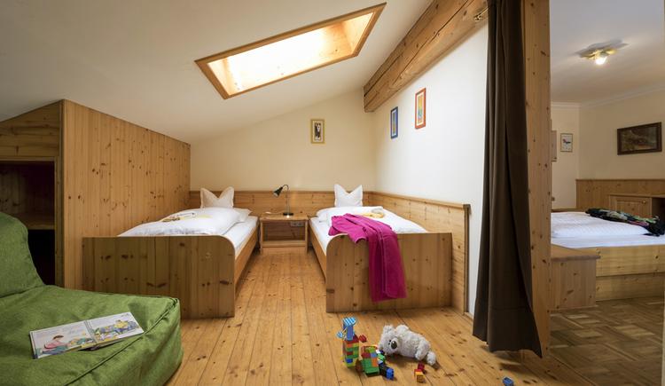 Kinderzimmer in der Dachschräge mit zwei einzelnen Betten und Verbindungstür zum Schlafzimmer der Eltern
