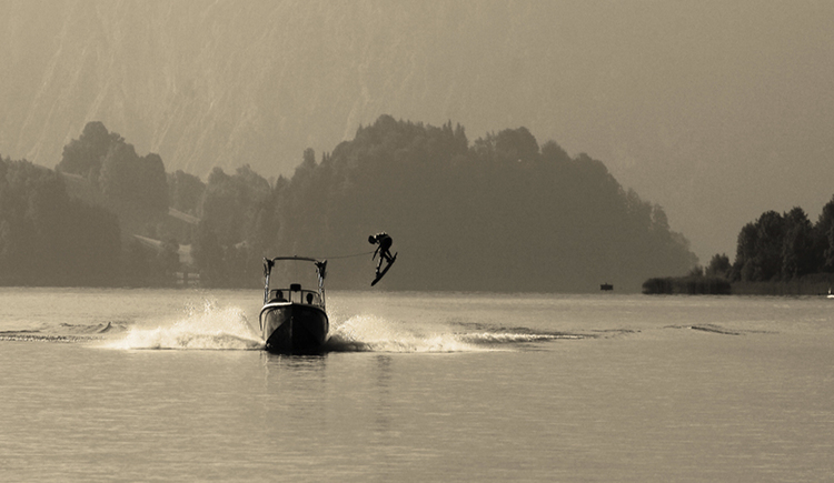 Motorboat on the lake, water skier in the air. (© Tourismusverband MondSeeLand)