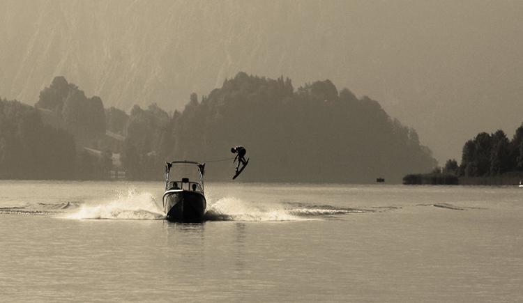 Motorboot auf dem See, Wasserskifahrer in der Luft. (© Tourismusverband MondSeeLand)