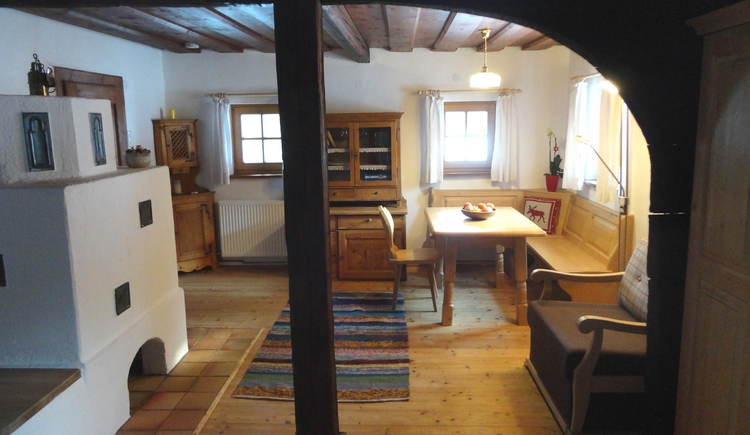 Spacious living and sleeping area furnished with lots of wood and romantic tiled stove.