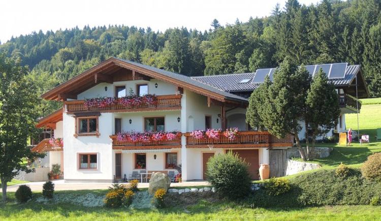 Blick auf das Haus mit Balkon und Blumen, im Vordergrund Wiesen, Sträucher, im Hintergrund ein Wald