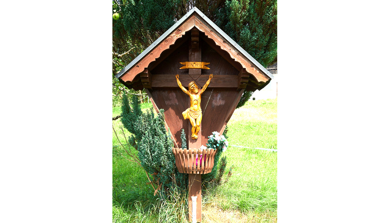 Blick auf das Kreuz, im Hintergrund Wiesen und Bäume
