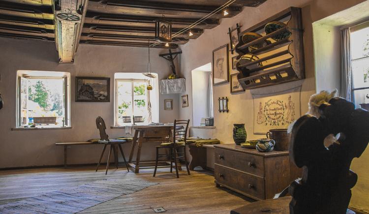 Alte Stube der Anzenaumühle mit traditioneller Holzdecke und Kommode