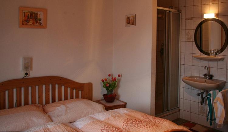 Schlafzimmer mit Doppelbett, Nachtkästchen, Blumen, im Hintergrund Dusche, Waschbecken, Spiegel