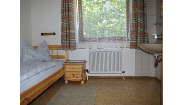 Schlafzimmer mit Einzelbett, Nachtkästchen, im Hinterrund ein Fenster, seitlich ein Waschbecken