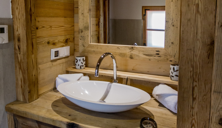 The modern equipped bathroom with lots of wood offers everything you need.