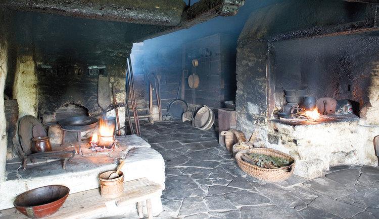 Feuerstelle im Rauchhaus mit alten Töpfen und Körben. (© www.mondsee.at)