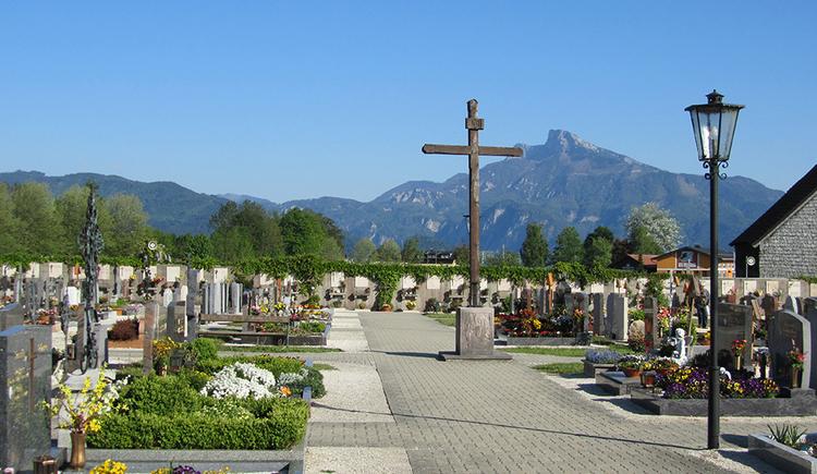 Blick auf den Friedhof in Mondsee im Hintergrund der Schafberg. Bildmittig das hölzerne Friedhofskreuz umsäumt von geschmückten Gräbern.