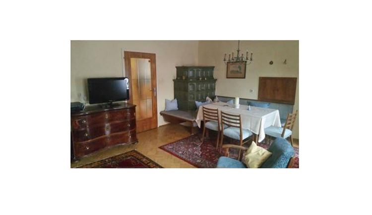 In the background chest of drawers with TV, tiled stove with oven, table and chairs