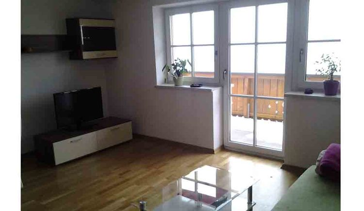 living area, TV on the chest of drawers and balcony door in the background