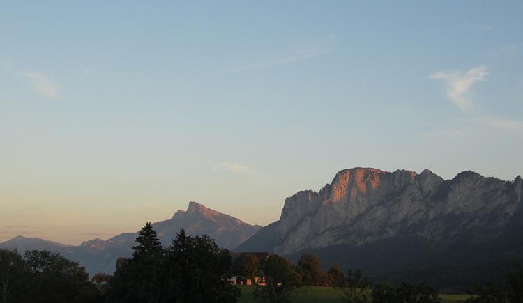 Ein Panoramablick, im Zentrum ein Bauernhof, dahinter der Schafberg, links das Drachenwandmassiv
