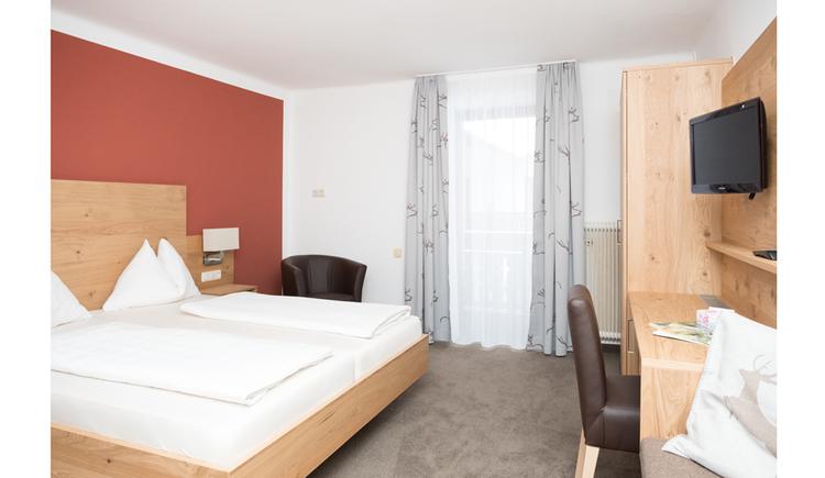 Doppelbett, seitlich ein Kleiderschrank, Stuhl, Fernseher an der Wand, im Hintergrund eine Balkontür