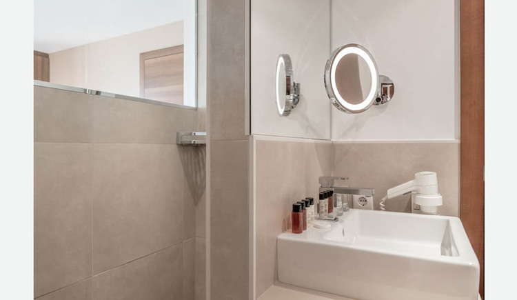 Bathroom with wash basin, hairdryer, cosmetic mirror, toiletries in small bottles