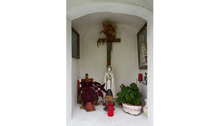 Blick auf Kerzen, Blumen, Heiligenfigur, Kreuz