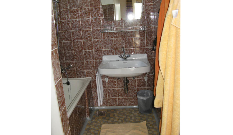 Bathroom with washbasin including a trash can, mirror, on the side towels are hanging on the wall, bathtub opposite