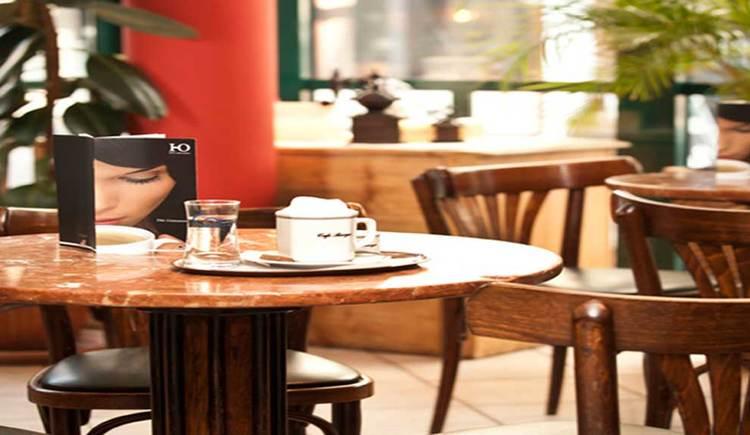 Tisch mit Stühlen, auf dem Tisch ein Cappuccino. (© Bäckerei-Cafe Berger)