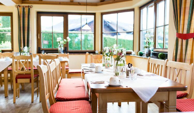 Gaststube, Tische mit Stühlen, gedeckte Tische mit Blumen. (© Aichingerwirt)