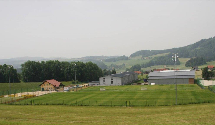 look at the sports field in the background Houses, forests, landscape. (© Tourismusverband MondSeeLand)