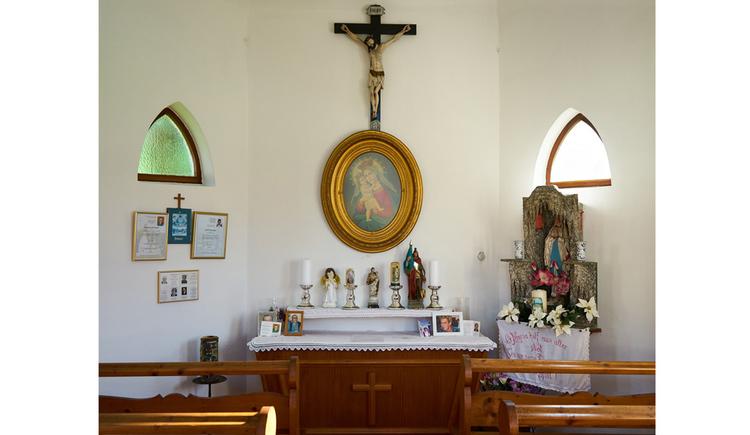 Blick auf den Altar mit Kerzen, darüber ein Marienbild und ein Kreuz, im Vordergrund Holzbänke