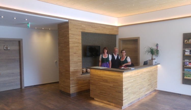 Here you will see the team of Hotel Goisererhof in the wooden reception area