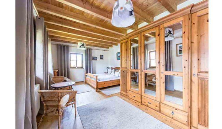 Schlafzimmer mit Doppelbett, im Vordergrund seitlich ein Kasten, Tisch und Stühle