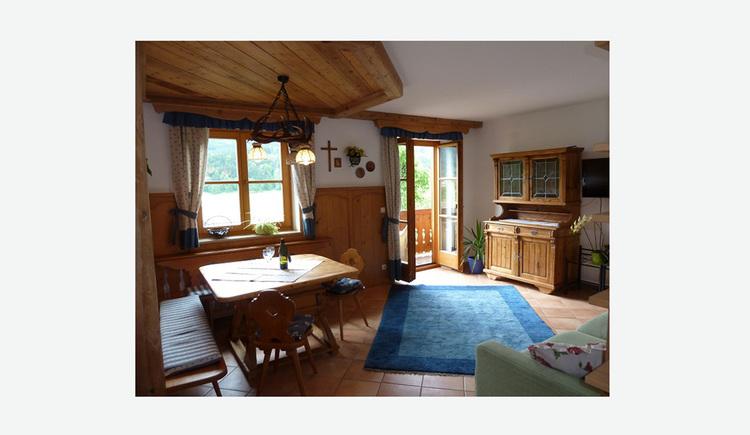 Wohnbereich mit Eckbank, Tisch, Stühle, seitlich eine Vollholzkommode mit Glasschrank, im Hintergrund Fenster und Türe