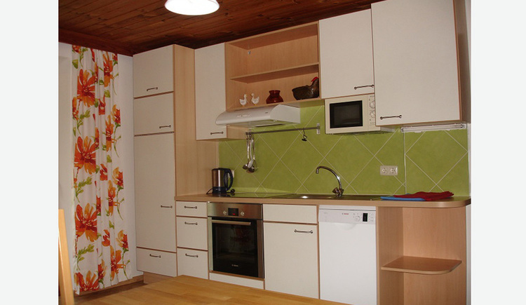 Kitchen with stove, kettle and microwave
