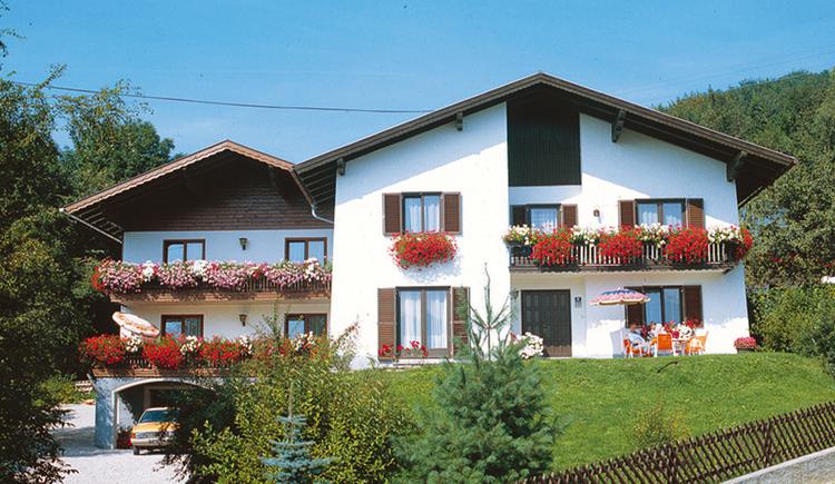 Blick auf das Doppelhaus, mit Balkon Blumen, davor Wiese