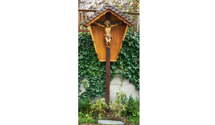 Blick auf das Holz Kreuz, im Hintergrund eine Mauer mit Pflanzen