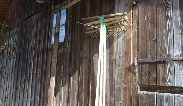 Holzrechen hängen auf einem Schuppen