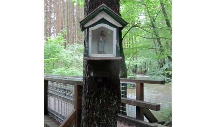 Baummarterl mit einer Heiligefigur hinter einem Glas, im Hintergrund eine Brücke, Bach, Bäume