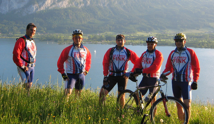 Cyclists in the meadow, in the background of the Mondsee