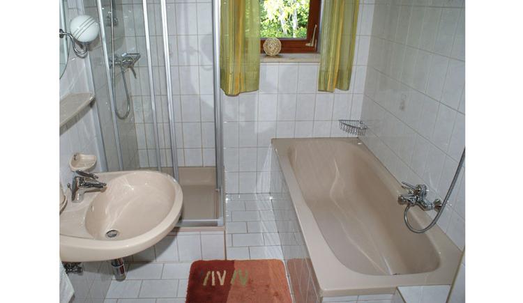 Badezimmer, seitlich Waschbecken, dahinter eine Duschkabine, Fenster, seitlich Badewanne