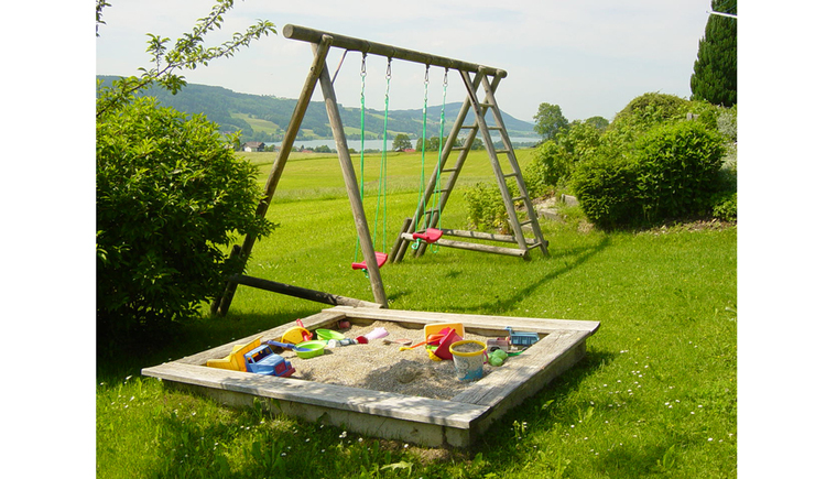 Swing and sandbox with toys in the meadow, in the background the lake and the mountains