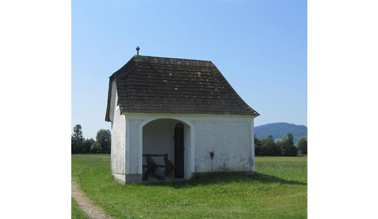 Blick auf eine Kapelle in einer Wiese, im Hintergrund Bäume, Berge