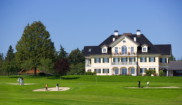 View at the house, in the foreground golf player at the golf course, trees