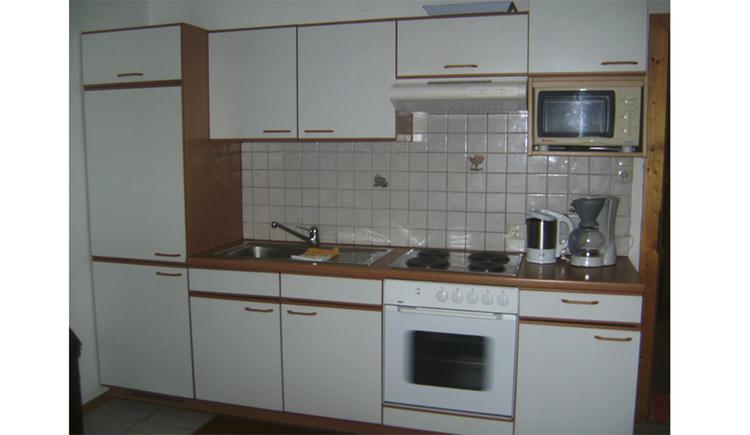 Küche mit Spüle, Herd, Wasserkocher, Kaffeemaschine, Mikrowelle