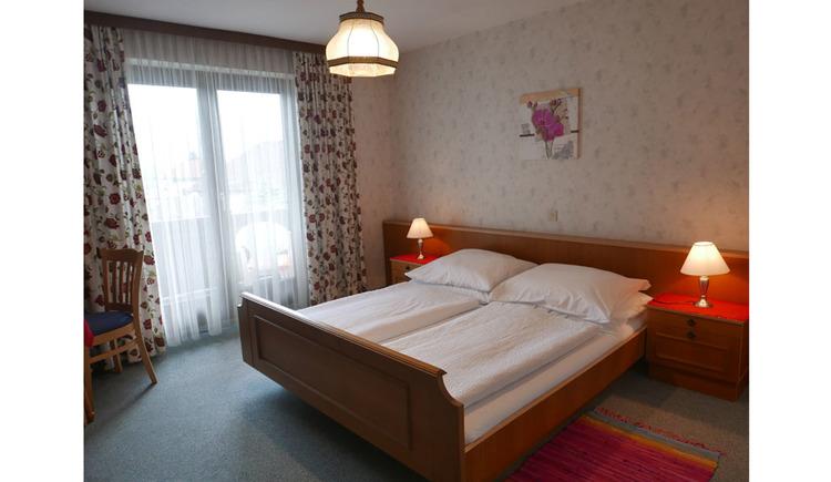 Schlafzimmer mit Doppelbett, Nachtkästchen, Tischlampen, seitlich eine Balkontür