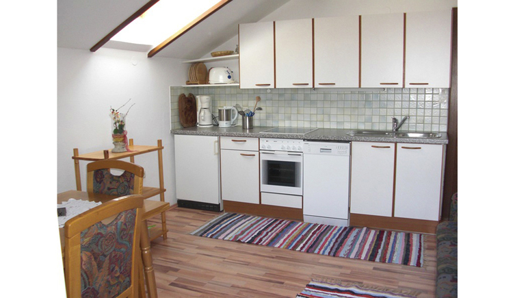 View into the kitchen with coffee machine, water cooker, stove, dishwasher, sink, in the foreground a table and chairs