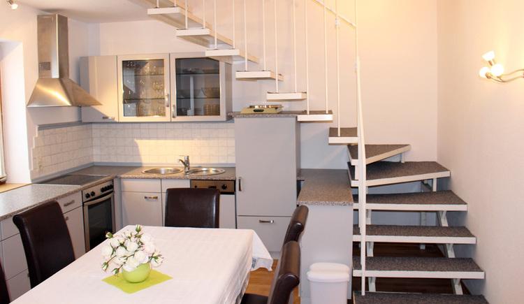 weiße Küche unter einer freistehenden Treppe  mit Tisch und braunen Sesseln im Vordergrund