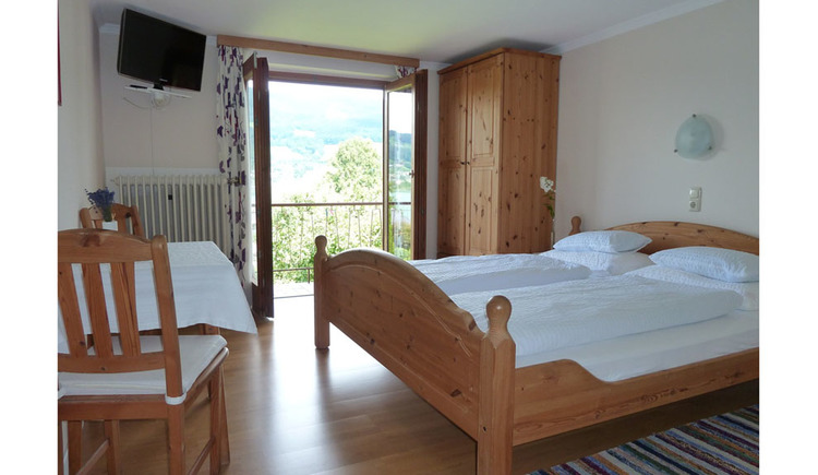 double bedroom with wardrobe, chairs and table on the side, open balcony door in the background, TV