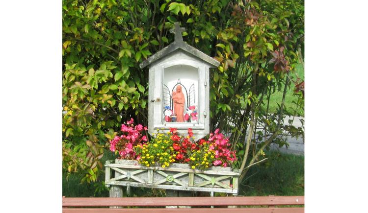 Blick auf das Marterl mit einer Heiligenfigur, darunter Blumen, im Hintergrund Sträucher