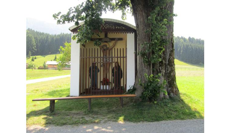 Blick auf die Kapelle mit Heiligen Figuren hinter einem Gitter, im Vordergrund eine Holzbank, seitlich ein Baum, im Hintergrund Landschaft