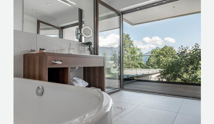 Bathtub, bathroom furniture on the side, view through the open terrace door to the countryside